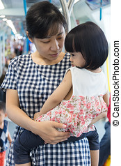 Asian Chinese mother carrying daughter inside a MRT transit...