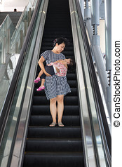 Asian Chinese mother carrying sleeping daughter taking...