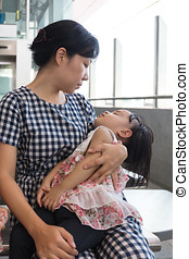 Asian Chinese mother carrying sleeping daughter inside a MRT...