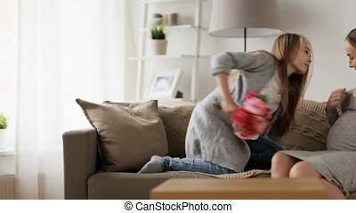 girl giving flowers to her pregnant mother at home -...