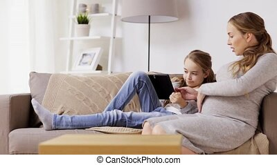 pregnant woman and girl with tablet pc at home - pregnancy,...