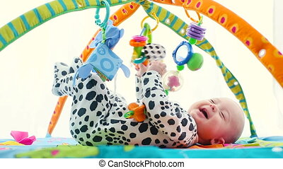 Happy baby boy smiling on playmat - Happy newborn lies on...