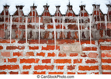 Icicles hang from the roof against a brick wall. Winter time