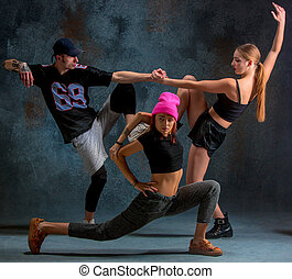 The two young girsl and boy dancing hip hop in the studio -...