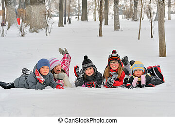 Happy children in winterwear laughing while playing in park