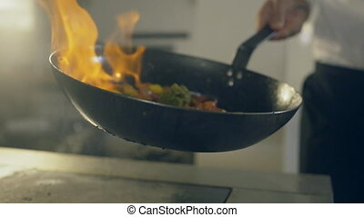 Chef in restaurant kitchen doing flambe on vegetables, close...