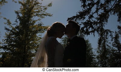 Bride and groom pose to photographer outdoor. Back light,...
