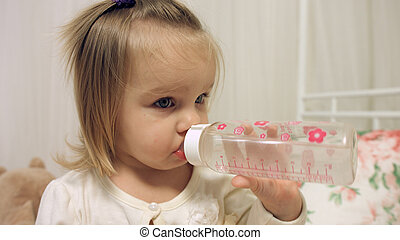 Adorable little girl drinks water from a bottle