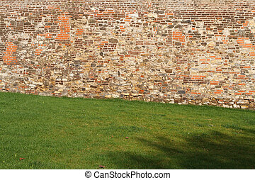 fragment of old brick fortress wall and green grass