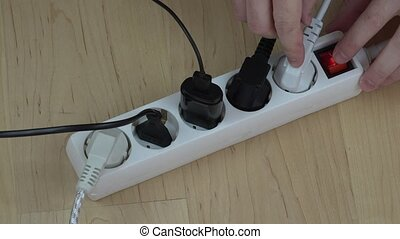 man hands turn off electricity extension switch and unplug...