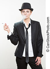 woman smokes a cigarette in business suit - Studio...
