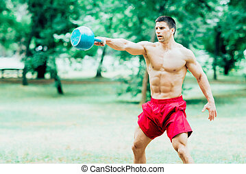 Kettle bell weight training - Muscular young man exercising...
