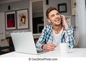 Happy man talking by phone while using laptop computer.