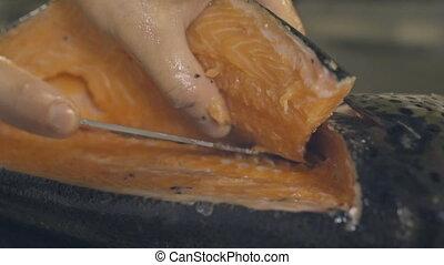 Chef preparing a fresh salmon on a cutting board, slow...