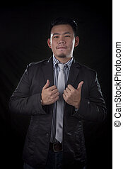 portrait of younger asian business man good working hand sign with studio lighting