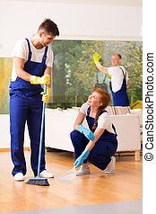 Man and woman sweeping floor - Man and woman wearing...