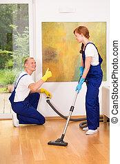 Woman vacuuming floor - Woman wearing uniform, vacuuming...