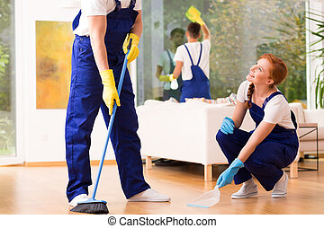 Cleaners sweeping floor - Professional cleaners wearing...