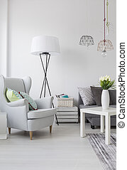 Bright living room with a white armchair and lamp - View of...