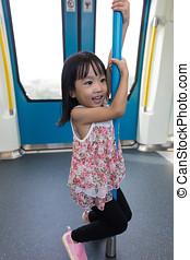 Asian Chinese little girl pole dancing inside a MRT transit...