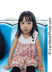 Asian Chinese little girl sitting inside a MRT transit in...
