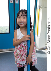 Asian Chinese little girl standing inside a MRT transit in...