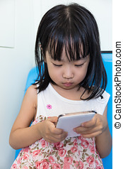 Asian Chinese little girl sitting inside a MRT with phone -...