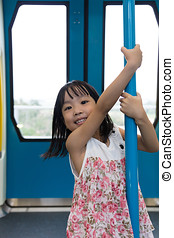 Asian Chinese little girl pole dancing inside a MRT transit...