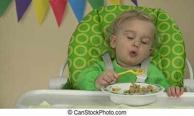 Independent baby boy with spoon sits at feeding chair and...