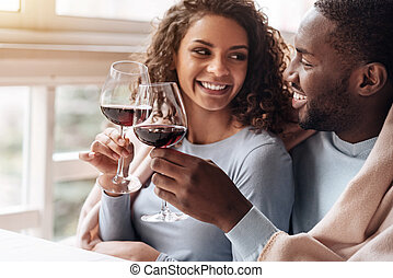 Positive African American couple holding wineglasses in the...