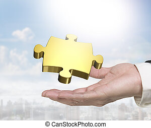 Man hand holding golden puzzle piece - Man's hand holding...