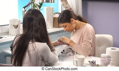 Woman manicure master doing manicure in spa nail salon