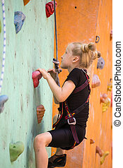 climbing up the bouldering wall - little girl climbing up...