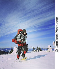 Winter hiking in the mountains on snowshoes with a backpack...
