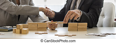Businessman shaking hands with wood blocks on desk -...