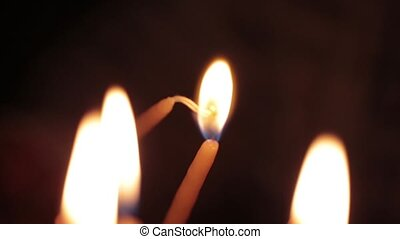 Hand holding a candle, going to burn a candle in church -...