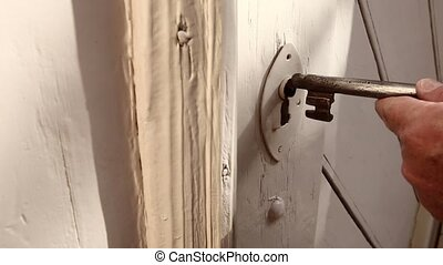 Old male hand Insert key into a ancient Door Lock - View of...