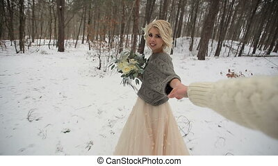 Beautiful Bride and Following Her Groom in Winter Forest