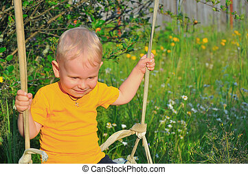 the little boy shakes on a swing in sunny summer day against...