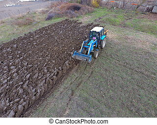 Tractor plowing the garden. Plowing the soil in the garden.