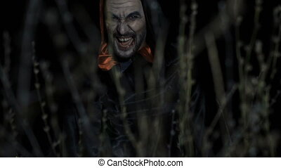 Horrible zombie scaring through the dead grass at night -...