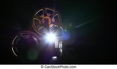 Film projector backlit from behind light lamp. Dark...