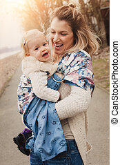 Young mother having her little daughter in baby carrier...