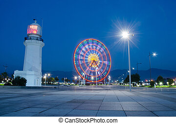 Night view of ferris wheel and old lighthouse located in Amusement Park at city seafront ,Batumi, Georgia.