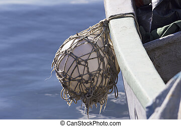 fender ball hanging of a fisher boat with blue sea - fender...
