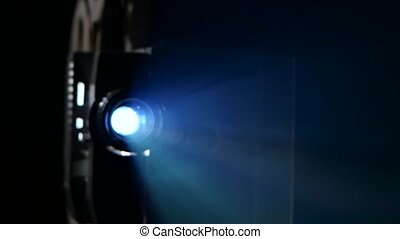 Lens cinema projector projecting the light beams onto the...