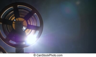 Reels twisting film on the projector in motion. Side view -...