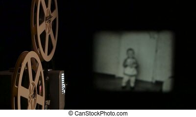 Vintage projector translates old film on the screen. Close...