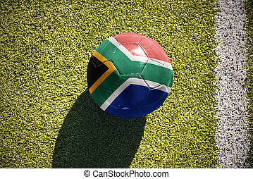 football ball with the national flag of south africa lies on the field