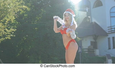 Glamour girl in santa hat dancing with Christmas decoration...